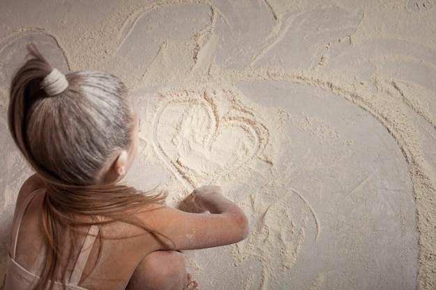 La fille tire son cœur sur la farine