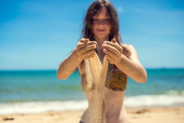 Fille touchant le sable sur la plage