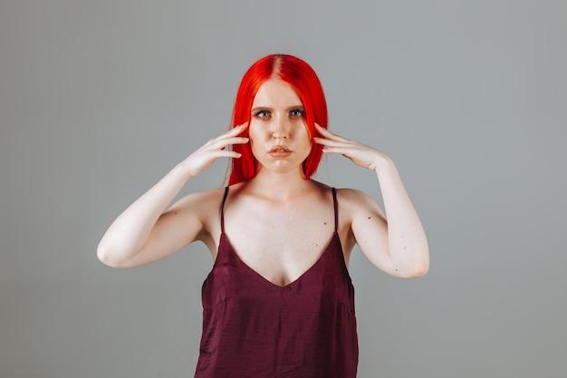 La fille touche ses longs cheveux rouges