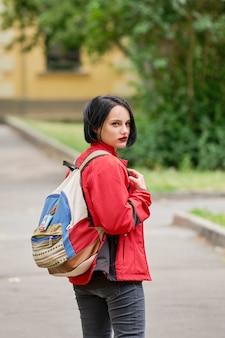 Fille de tourisme avec sac à dos en toile regardant dans la rue