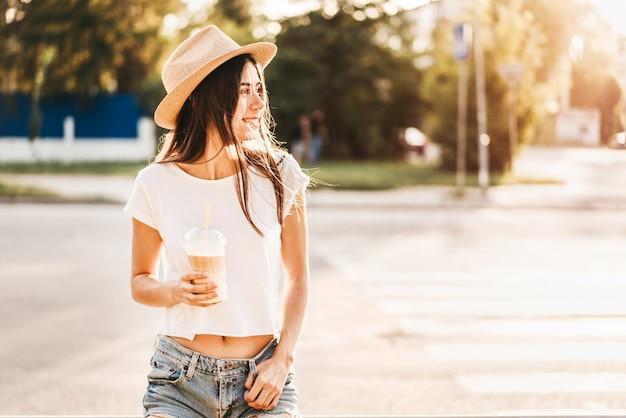 Fille de touriste jolie brune avec une tasse de café froid en plein air.