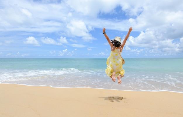 Une fille touristique heureuse et énergique saute à la plage pendant les vacances d'été, le plaisir et la liberté avec de nouveaux concepts de voyage normaux