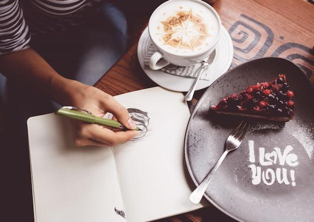 Fille en train de dessiner une tasse de café dans le cahier