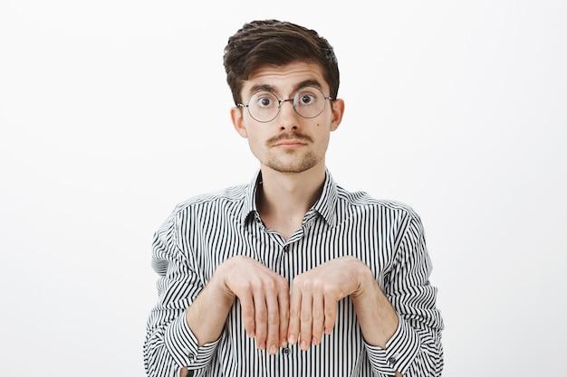 Fille transformée en petit ami en chiot. portrait d'un homme caucasien drôle mignon avec moustache dans des verres, tenant les mains près de la poitrine comme des pattes d'animaux et regardant avec une expression insouciante et stupide