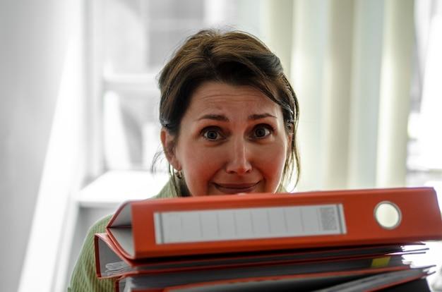 Fille de travail d'entreprise avec de nombreux documents de bureau en face de la tête