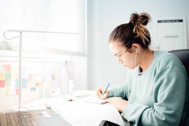 Fille travaillant sur un ordinateur portable à la maison ou étudiant étudiant à domicile ou indépendant. travail en ligne, travail de bureau tard le soir, bureau à domicile