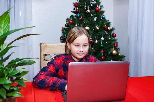 La fille travaille derrière l'ordinateur portable à l'arrière-plan de l'arbre de noël