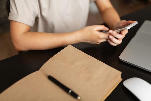 La fille travaille à domicile vérifie les informations du téléphone sur l'ordinateur