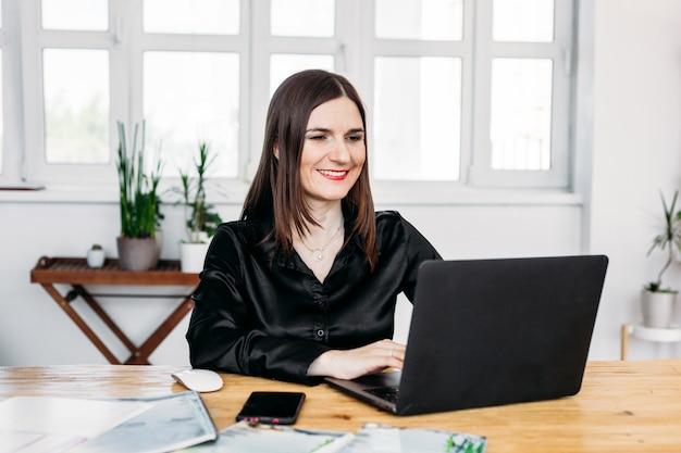 Fille travaille ordinateur, communication des clients, table d'ordinateur portable, un ordinateur, un pot avec une fleur, une souris d'ordinateur portable, travail et internet, maison