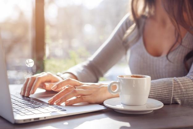 Une fille travaille sur un ordinateur portable dans un café par une journée ensoleillée