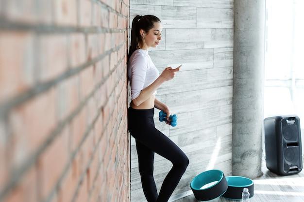 Fille travaille avec son smartphone après ou avant un entraînement dans la salle de gym