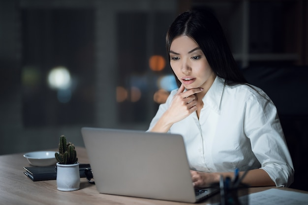 Fille travaille tard dans le bureau sombre avec un ordinateur portable.