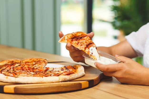 Une fille trempe une part de pizza en sauce dans un récipient en plastique avant de la manger