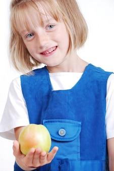 Une fille très mignonne, mangeant une pomme isolée