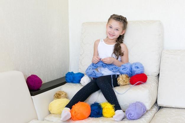 La fille tricote avec du tricot et du fil.