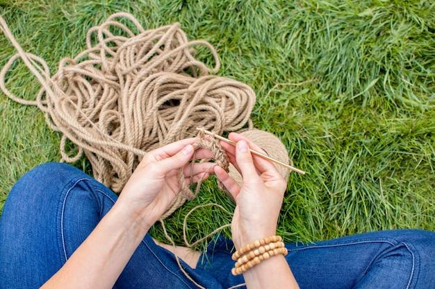 Fille tricote un panier au crochet sur l'herbe, assis dans le jardin sur l'herbe. passe-temps à la maison.