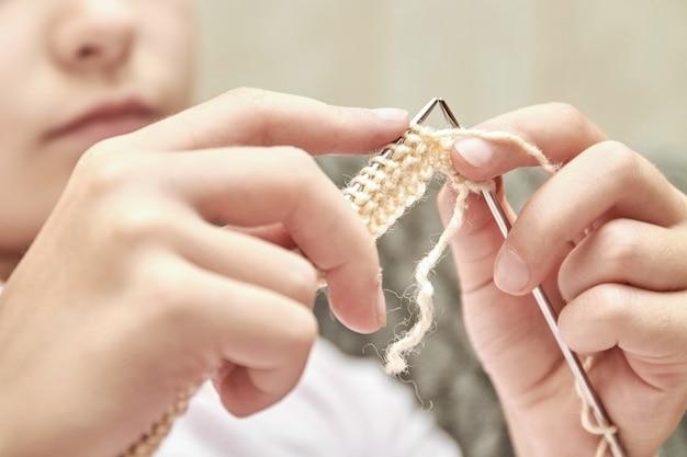 Une fille tricote un pull chaud beige
