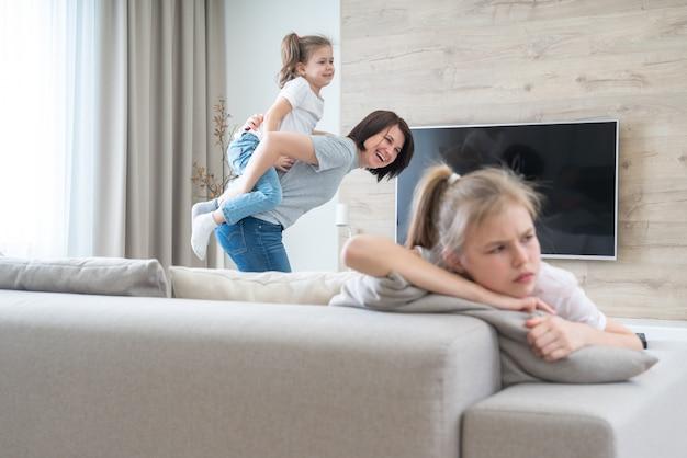Fille triste assise sur un canapé pendant que la mère s'amuse avec sa sœur