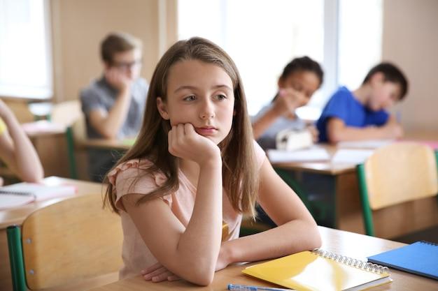 Fille triste assise dans la salle de classe.