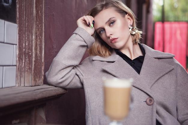 Fille triste assise triste dans un café de la rue avec une tasse de délicieux cappuccino