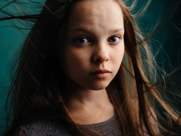 Fille triste aux cheveux ébouriffés sur fond turquoise dans une robe grise. photo de haute qualité