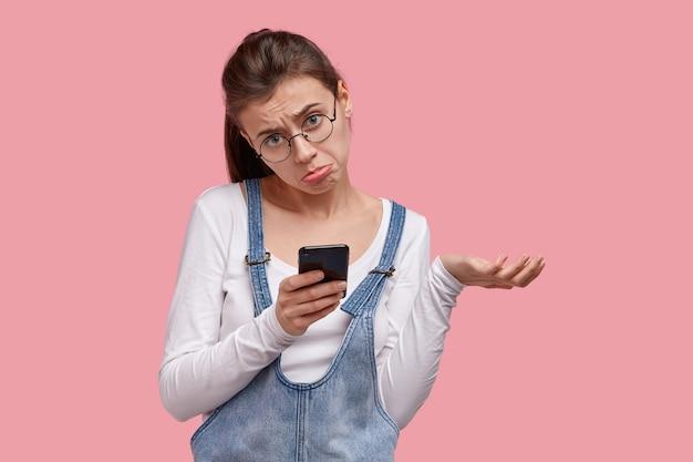 Une fille triste bouleversée porte une bourse à la lèvre inférieure, lève la main, fait la grimace du désespoir, tient un smartphone, lit des nouvelles décevantes, a l'air abattu