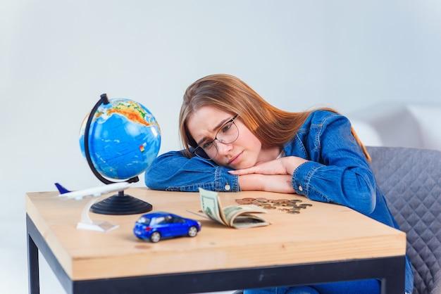 Une fille triste compte ses économies et ses rêves de voyages et de véhicules personnels. concept d'argent d'épargne.