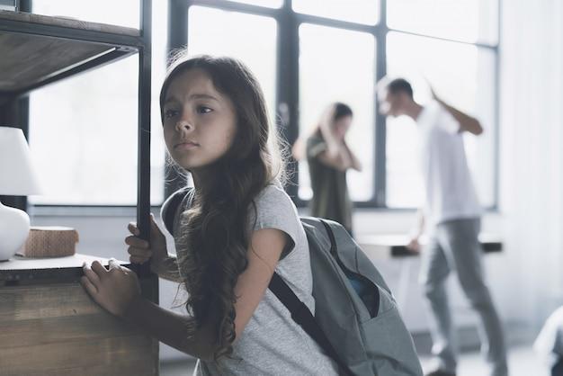 Une fille triste écoute comment les parents se battent à la maison