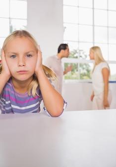Fille triste avec des parents qui se battent
