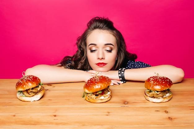Fille triste en regardant délicieux hamburgers frais avec du poulet sur tablable en bois
