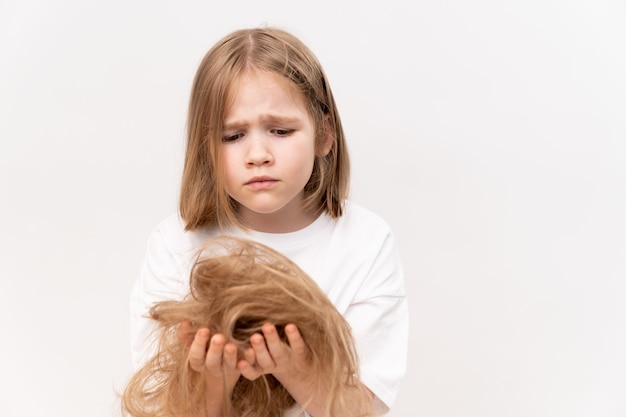 Une fille triste tient dans les mains les cheveux coupés après avoir coupé sur un fond blanc. signifie prendre soin des cheveux des enfants. salon de beauté pour enfants.