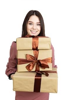 Fille avec trois coffrets cadeaux dans ses mains. une jeune fille brune aux cheveux longs détient trois cadeaux dans ses mains, isoler