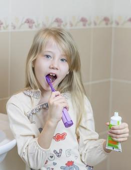 Fille avec un tube ouvert de dentifrice et une brosse à dents électrique.