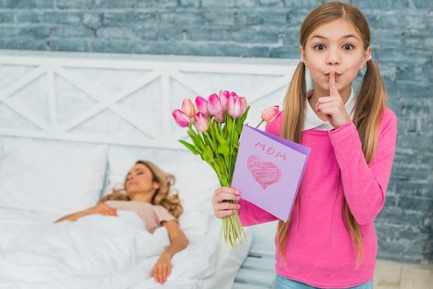 Fille avec des tulipes et carte de voeux tenant un doigt sur les lèvres