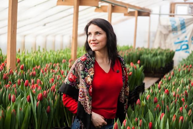 Fille avec des tulipes cultivées dans une serre.
