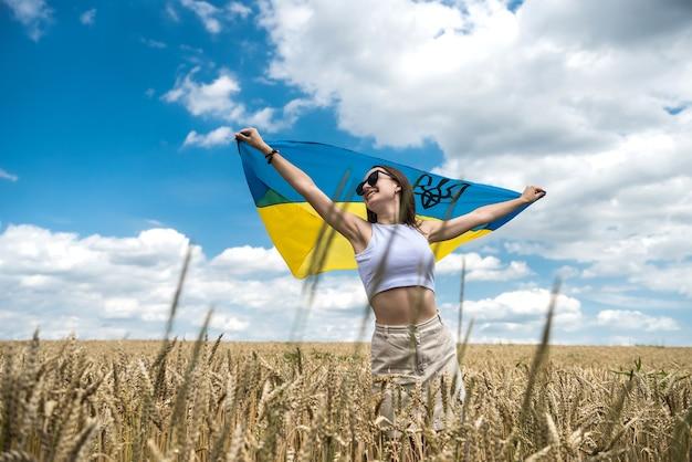 Fille ukrainienne de mode avec drapeau national sur champ de blé en été