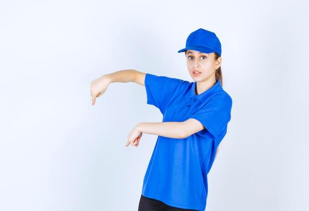 Fille en uniforme bleu montrant quelque chose ci-dessous.