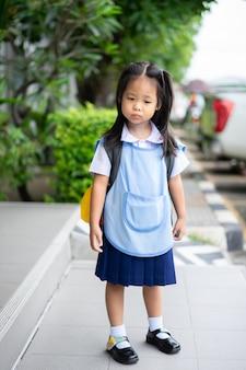 Fille en uniforme d'école thaïlandaise debout dans le parc, pas prête pour la rentrée scolaire