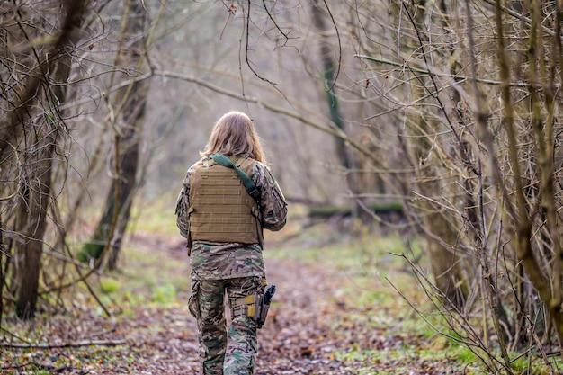 Fille en uniforme militaire avec un pistolet airsoft marchant sur un chemin de terre dans la forêt
