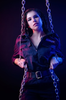Une fille en uniforme de police avec des dreadlocks en néon avec des chaînes et des menottes traduction en anglais la police