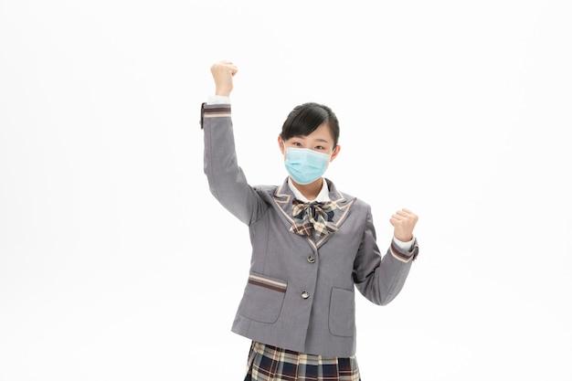 Fille en uniforme scolaire portant un masque avec énergie