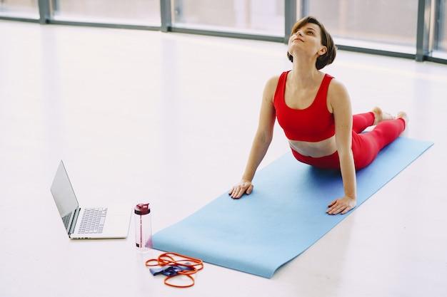 Fille en uniforme de sport rouge pratiquant le yoga à la maison