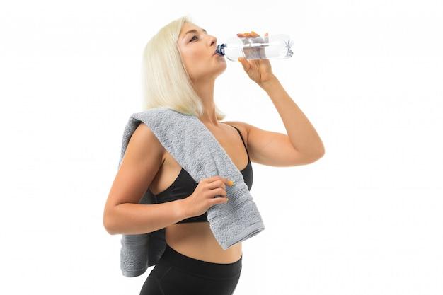 Fille en uniforme de sport avec une serviette et une bouteille d'eau sur un studio blanc