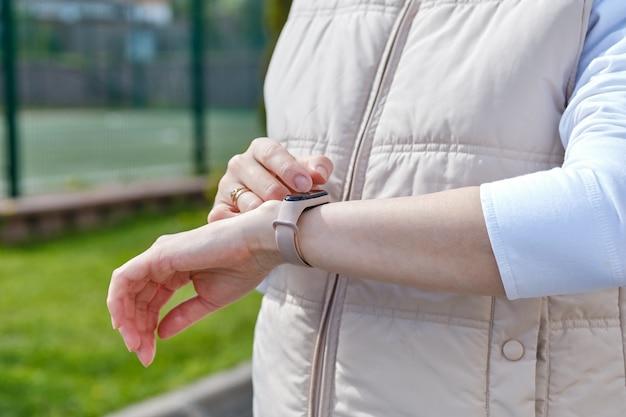 Une fille utilise une montre intelligente sur sa main en marchant dans la rue.