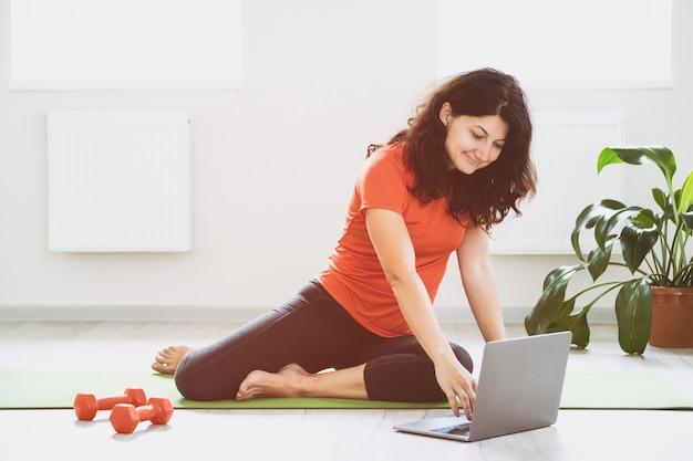 Une fille utilise un ordinateur portable pendant une séance d'entraînement en ligne - une jeune fille fait une séance d'entraînement à la maison dans une pièce