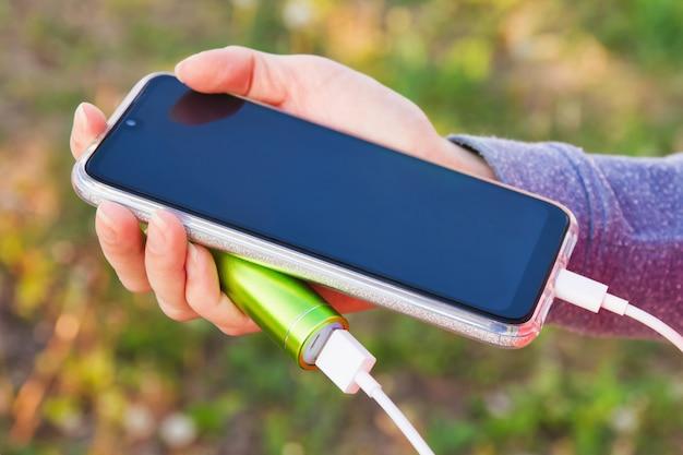 Une fille utilise un smartphone à l'extérieur pendant la charge à partir d'une banque d'alimentation externe