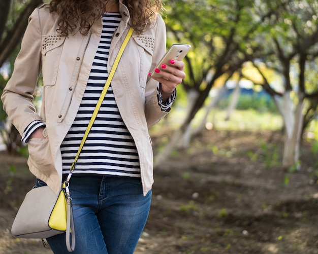 Fille utilise un téléphone dans une veste beige et un jean bleu