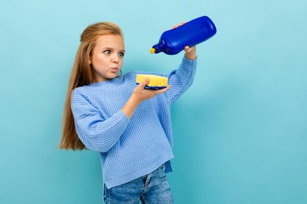 Fille va laver la vaisselle avec un gant de toilette et un détergent isolé sur bleu