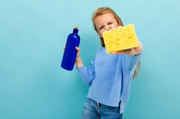 Fille va laver la vaisselle avec un gant de toilette et un détergent isolé sur fond bleu