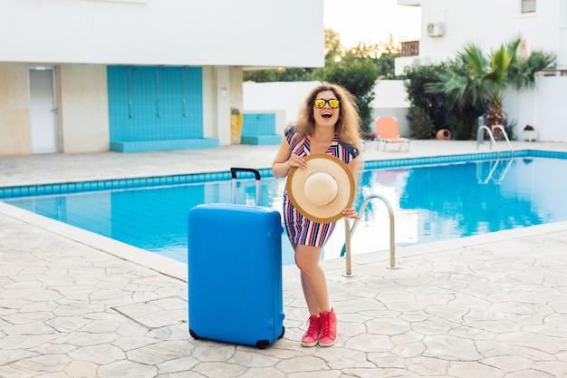 Fille en vacances d'été contre piscine, robe rayée habillée et lunettes de soleil.